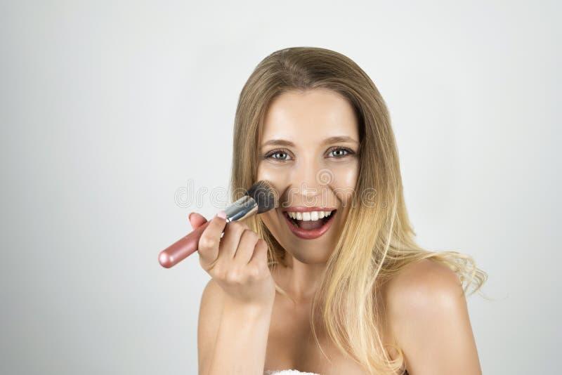 Νέα όμορφη ξανθή χαμογελώντας γυναίκα που βάζει makeup με το ρόδινο απομονωμένο brushe άσπρο υπόβαθρο στοκ φωτογραφία