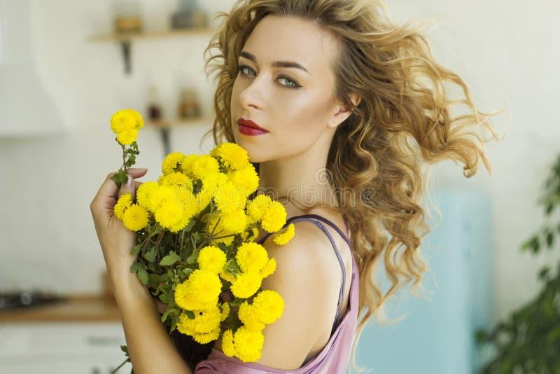 Νέα όμορφη ξανθιά γυναίκα με ροζ πρωινή φορεσιά με κίτρινα λουλούδια στην κουζίνα της στοκ φωτογραφία με δικαίωμα ελεύθερης χρήσης