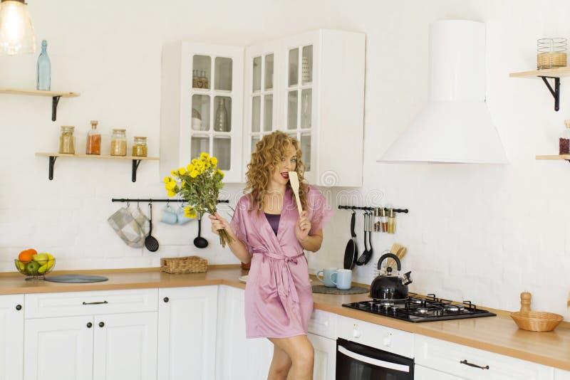 Νέα όμορφη ξανθιά γυναίκα με ροζ πρωινή φορεσιά με κίτρινα λουλούδια στην κουζίνα της στοκ εικόνες με δικαίωμα ελεύθερης χρήσης