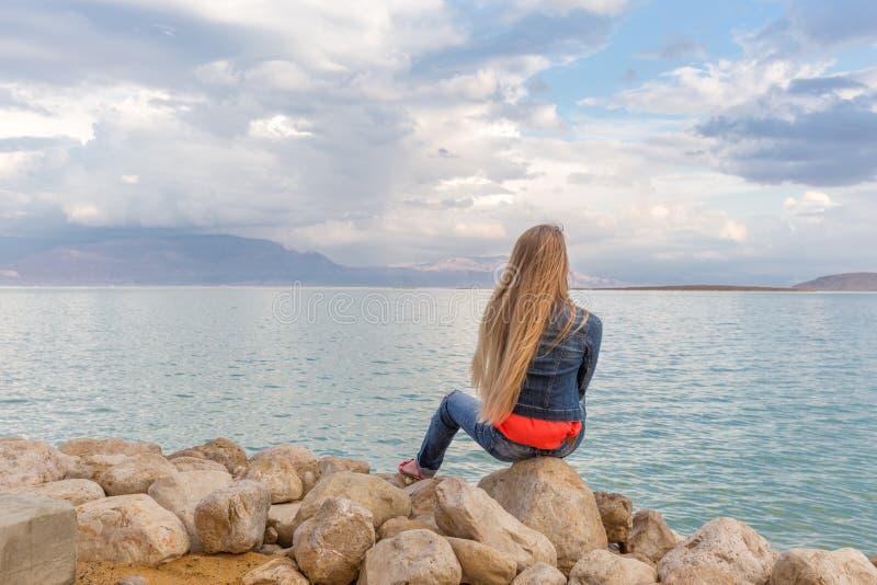 Νέα όμορφη παραλία θάλασσας πετρών συνεδρίασης γυναικών blondie στοκ φωτογραφίες με δικαίωμα ελεύθερης χρήσης