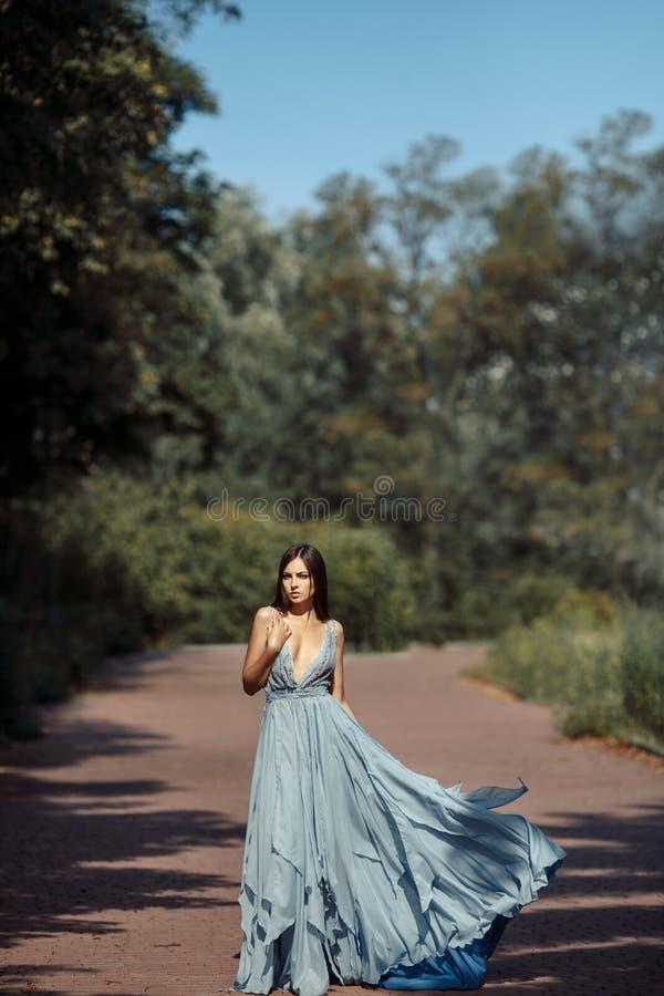 Νέα όμορφη πορεία περπατήματος φορεμάτων γυναικών μπλε στο πάρκο στοκ φωτογραφίες