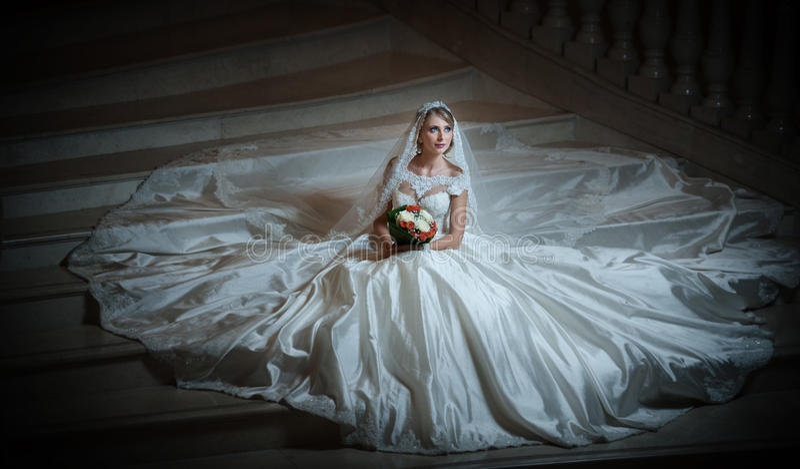 Νέα όμορφη πολυτελής γυναίκα στη συνεδρίαση γαμήλιων φορεμάτων στα βήματα σκαλοπατιών στο ημι-σκοτάδι Νύφη με το τεράστιο γαμήλιο στοκ φωτογραφίες με δικαίωμα ελεύθερης χρήσης