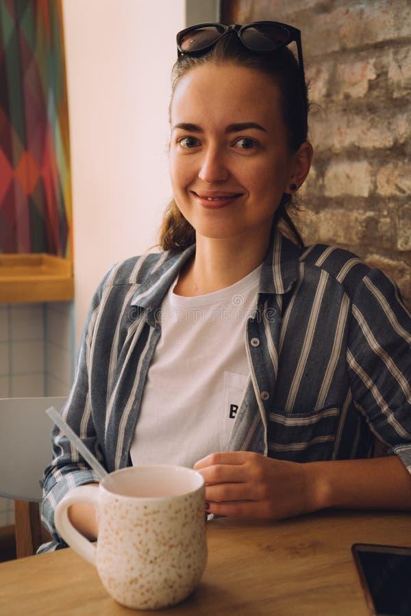 Νέα όμορφη συνεδρίαση γυναικών σε έναν καφέ και ομιλία στο τηλέφωνο Το κορίτσι πίνει τον καυτό καφέ στοκ εικόνα