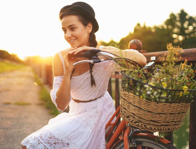 Νέα όμορφη συνεδρίαση γυναικών στο ποδήλατό της με τα λουλούδια στον ήλιο στοκ φωτογραφία με δικαίωμα ελεύθερης χρήσης