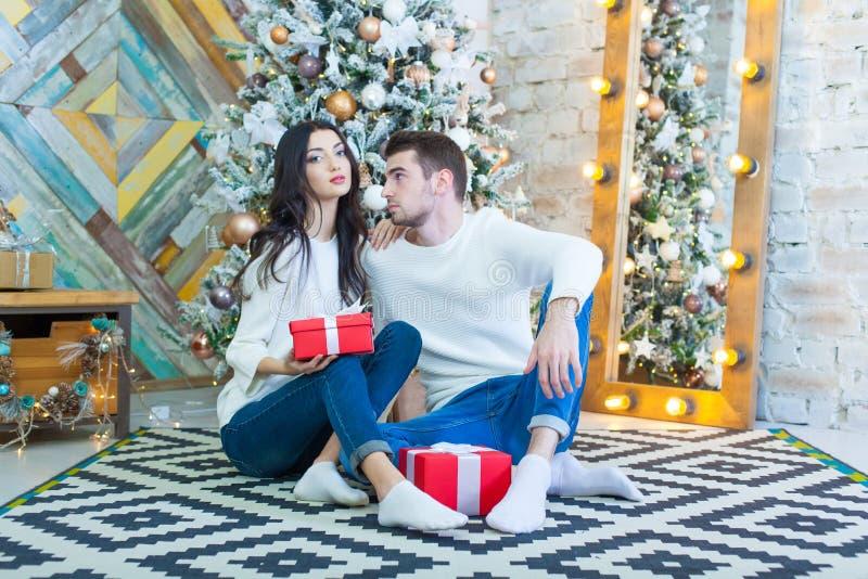 Νέα όμορφη συνεδρίαση ζευγών κοντά στο χριστουγεννιάτικο δέντρο με το κόκκινο boxe giftsin Χριστουγέννων στοκ εικόνες