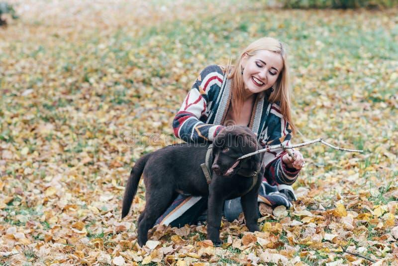 Νέα όμορφη συνεδρίαση κοριτσιών στην εποχή πάρκων το φθινόπωρο και παιχνίδι με ένα μαύρο κουτάβι στοκ εικόνες