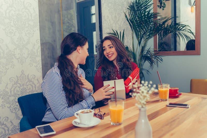 Νέα όμορφη συνεδρίαση κοριτσιών στον καφέ με το φίλο της και τη λήψη ενός δώρου στοκ εικόνα με δικαίωμα ελεύθερης χρήσης