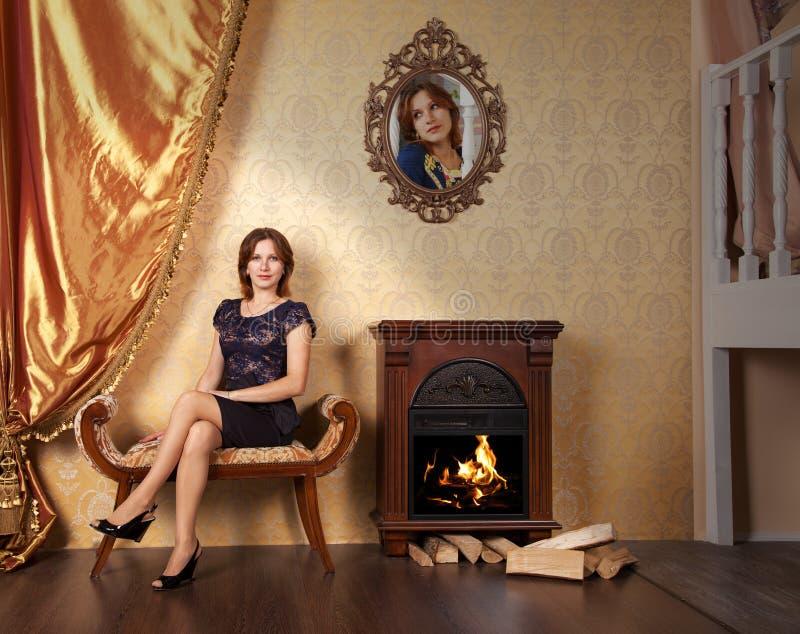 Νέα όμορφη συνεδρίαση γυναικών σε έναν καναπέ στο δωμάτιο στοκ εικόνες