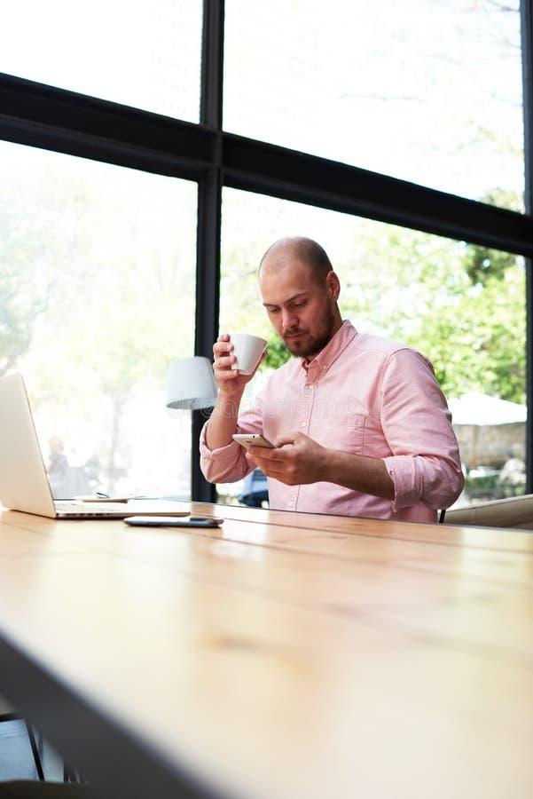 Νέα όμορφη συνεδρίαση προγραμματιστών στον καφέ και ομιλία στο τηλέφωνο στοκ εικόνα με δικαίωμα ελεύθερης χρήσης