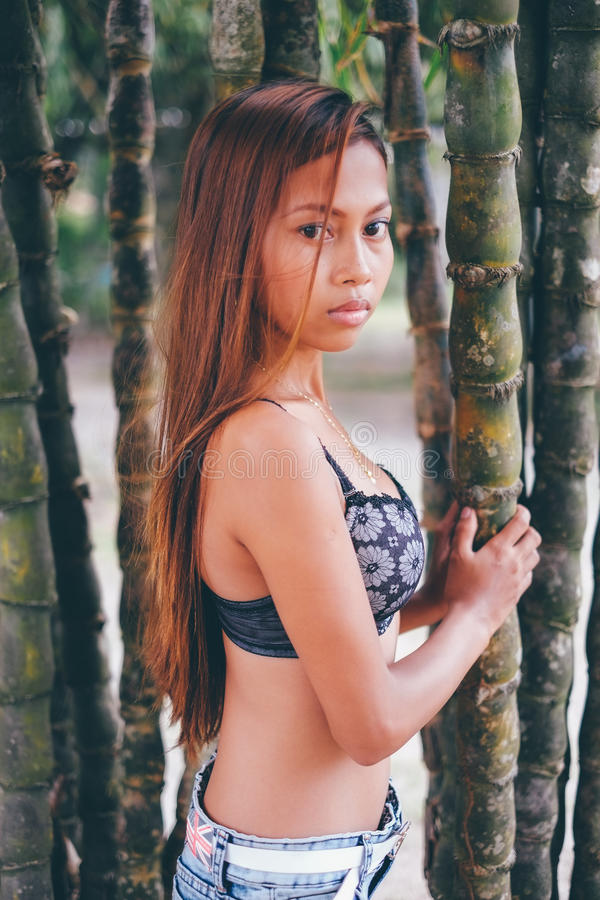 Νέα όμορφη τοποθέτηση κοριτσιών με τα δέντρα bamoo, καυτή έννοια θερινής μόδας στοκ φωτογραφία