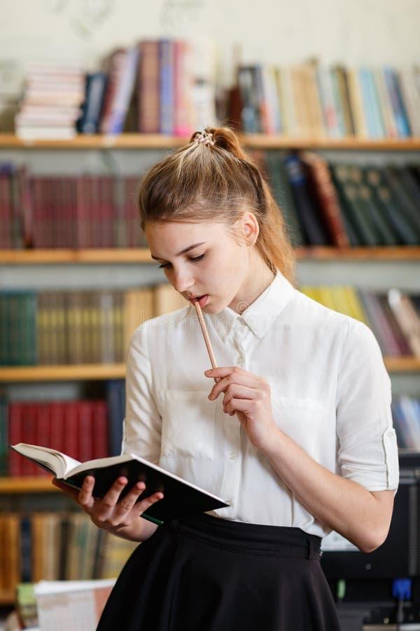 Νέα όμορφη τοποθέτηση κοριτσιών στη κάμερα στη βιβλιοθήκη η εκπαίδευση έννοιας βιβλίων απομόνωσε παλαιό στοκ εικόνες