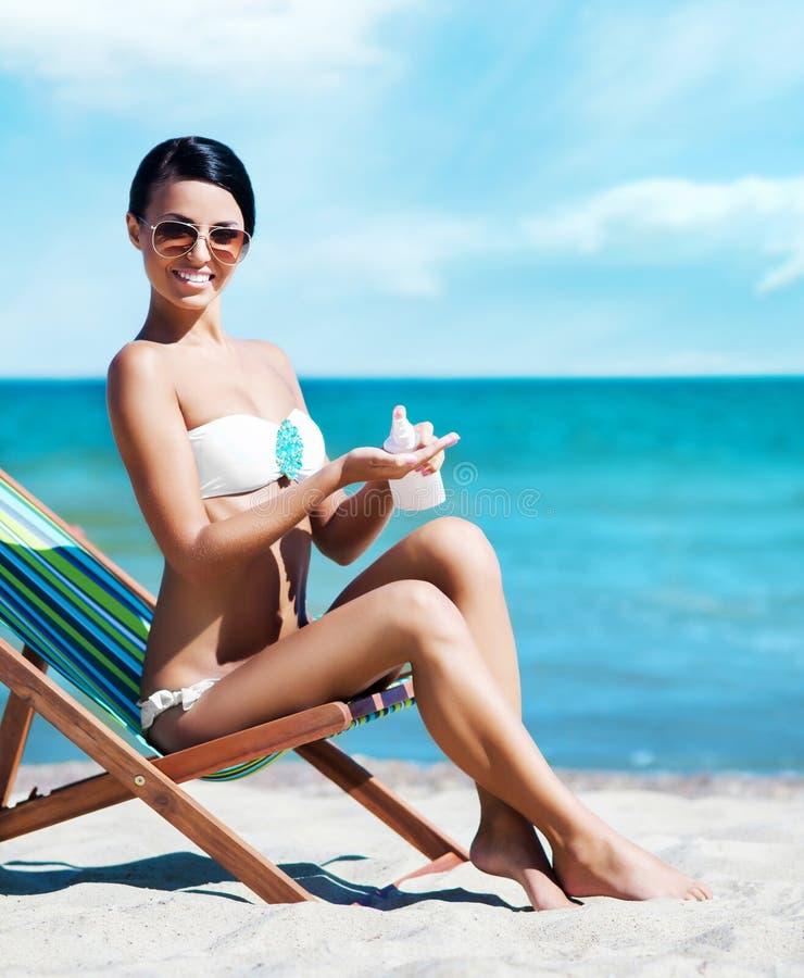 Νέα, όμορφη, φίλαθλη και προκλητική γυναίκα που χρησιμοποιεί τη suntan κρέμα ο στοκ εικόνες με δικαίωμα ελεύθερης χρήσης