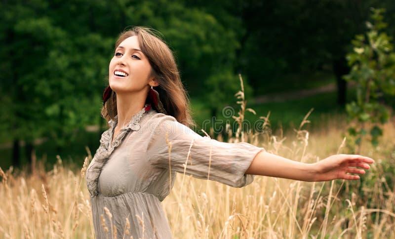 Νέα όμορφη χαμογελώντας γυναίκα με τα αυξημένα όπλα στοκ εικόνες