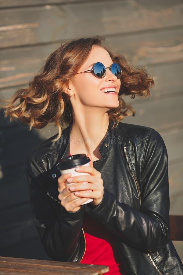 Νέα όμορφη χαμογελώντας γυναίκα στα στρογγυλά γυαλιά που πίνει τον καφέ στοκ φωτογραφίες