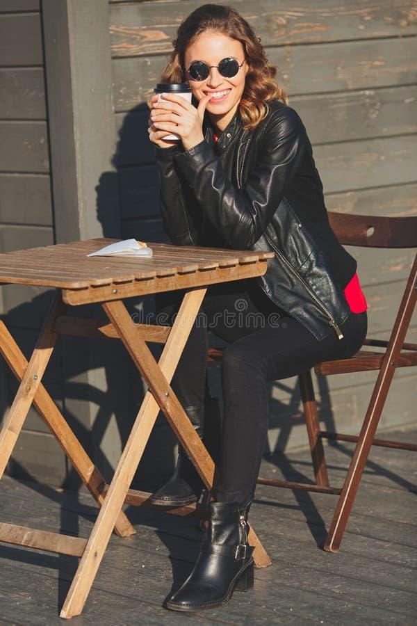 Νέα όμορφη χαμογελώντας γυναίκα στα στρογγυλά γυαλιά που πίνει τον καφέ στοκ φωτογραφία με δικαίωμα ελεύθερης χρήσης