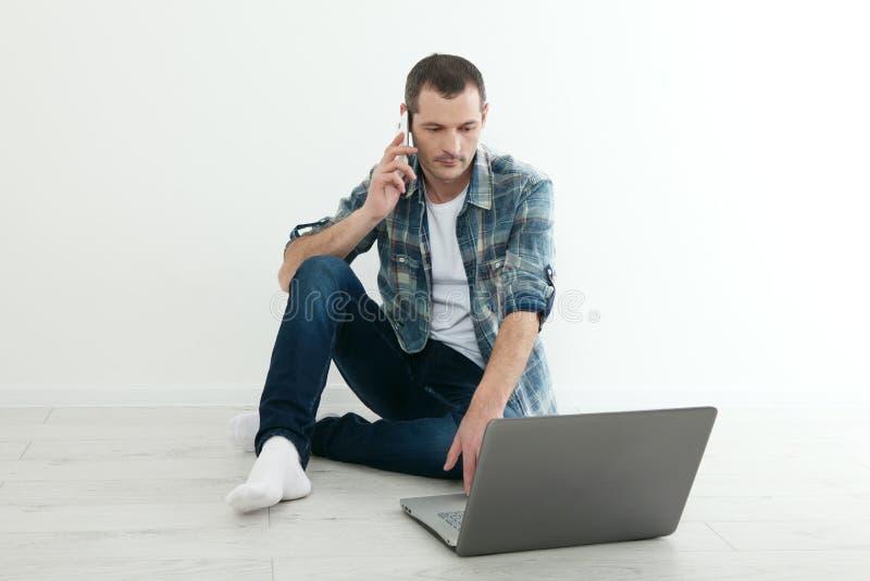 Νέα όμορφη χαλάρωση ατόμων στο πάτωμα και χρησιμοποίηση του lap-top, έξυπνο τηλέφωνο στο σπίτι στοκ εικόνες