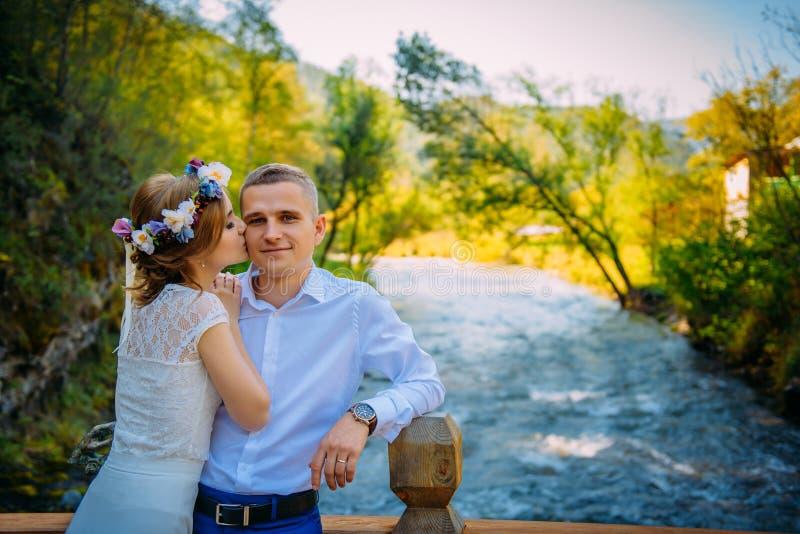 Νέα beautyful νύφη με τον κυκλίσκο των λουλουδιών που φιλά τον ευτυχή σύζυγο Στο υπόβαθρο, άγριοι δέντρα φύσης και ποταμός βουνών στοκ εικόνα