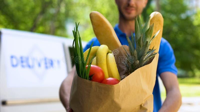 Νέα deliveryman παρουσιάζοντας τσάντα παντοπωλείων, υπηρεσία καταστημάτων, σε απευθείας σύνδεση αποστολή διαταγής στοκ φωτογραφίες