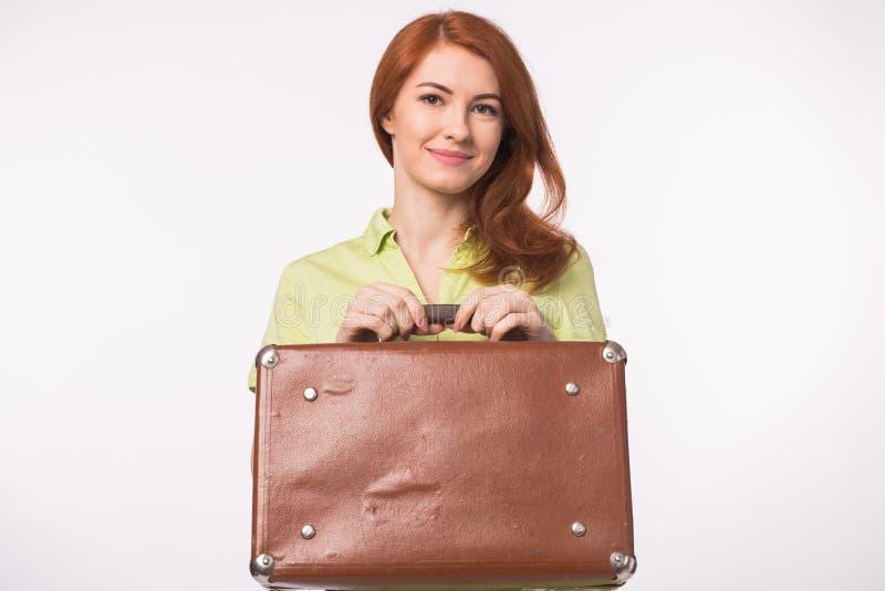 Νέα redhead γυναίκα με την εκλεκτής ποιότητας βαλίτσα δέρματος στο άσπρο υπόβαθρο στοκ εικόνα