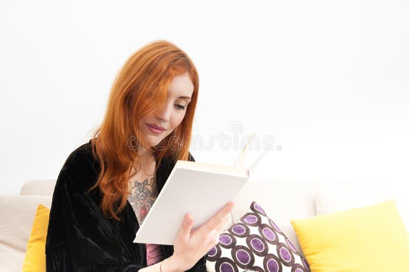 Νέα redhead γυναίκα που χαμογελά και που διαβάζει ένα βιβλίο στοκ εικόνα