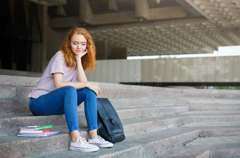 Νέα redhead συνεδρίαση κοριτσιών σπουδαστών στα σκαλοπάτια υπαίθρια στοκ φωτογραφίες