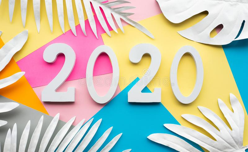 2020 νέες έννοιες εορτασμού έτους παρουσιάζουν τη διακόσμηση αριθμού κειμένων με το τροπικό φύλλο στο ζωηρόχρωμο υπόβαθρο στοκ εικόνες