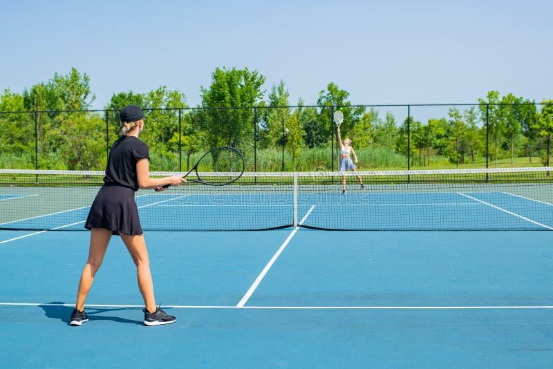 Νέες αθλήτριες που παίζουν την αντισφαίριση στο μπλε γήπεδο αντισφαίρισης στοκ εικόνες