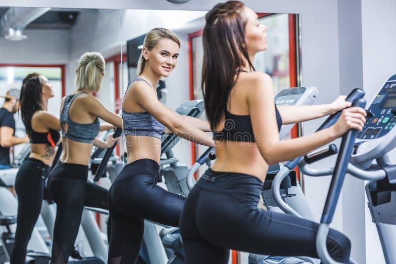 νέες αθλητικές γυναίκες που επιλύουν στις ελλειπτικές μηχανές στοκ φωτογραφίες