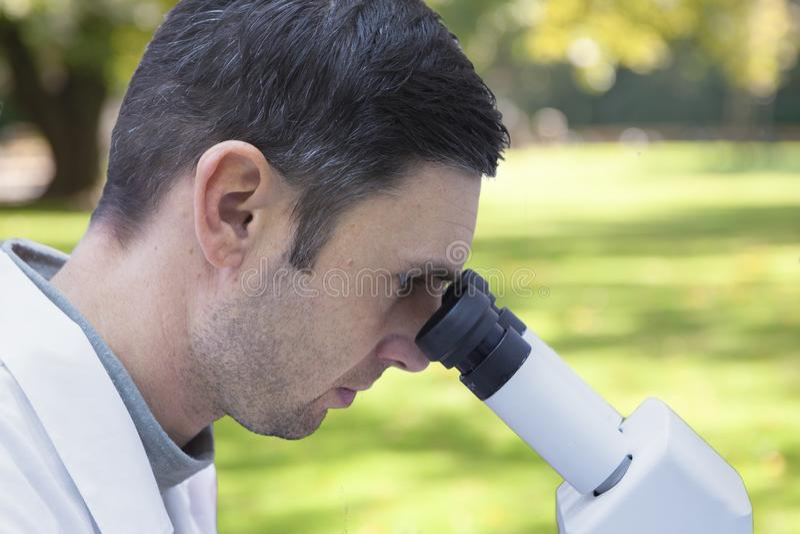 Νέες αρσενικές εργασίες επιστημόνων με ένα μικροσκόπιο σε ένα εργαστήριο επιστήμης στοκ εικόνες