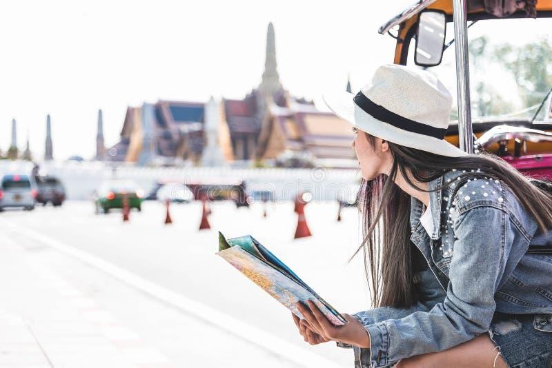 Νέες ασιατικές γυναίκες που κάθονται στο τοπικό ταξί που τρυπά έναν χάρτη με το μεγάλο παλάτι ως θολωμένο υπόβαθρο, Μπανγκόκ Ταϊλ στοκ εικόνες
