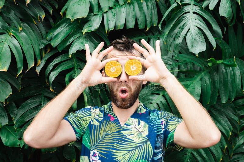 Νέες γενειοφόρες φέτες εκμετάλλευσης ατόμων πορτοκαλί tangerine μπροστά από τα μάτια του, έκπληκτες στοκ φωτογραφία με δικαίωμα ελεύθερης χρήσης