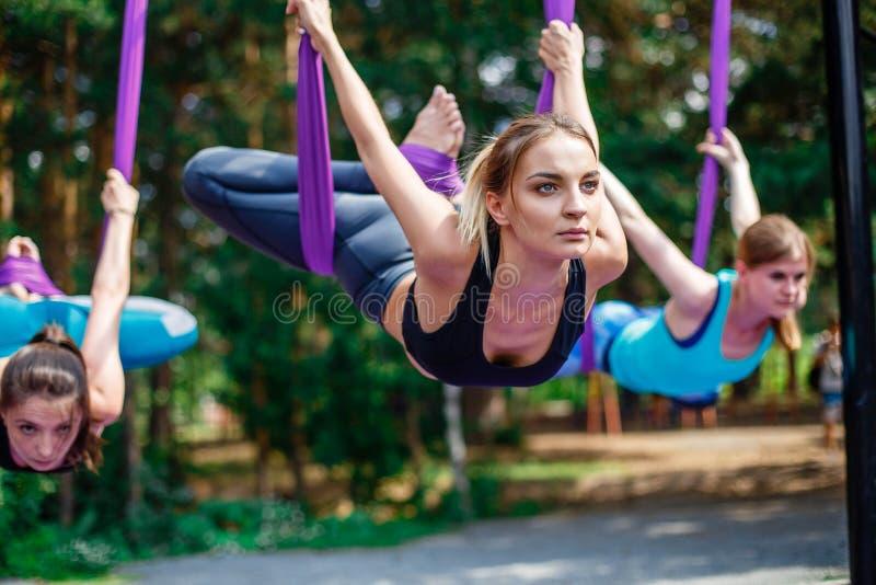 Νέες γυναίκες, ενάντιες στη βαρύτητα ασκήσεις γιόγκας με μια ομάδα ανθρώπων υπαίθρια εκπαιδευτής ικανότητας μυγών aero στοκ εικόνες