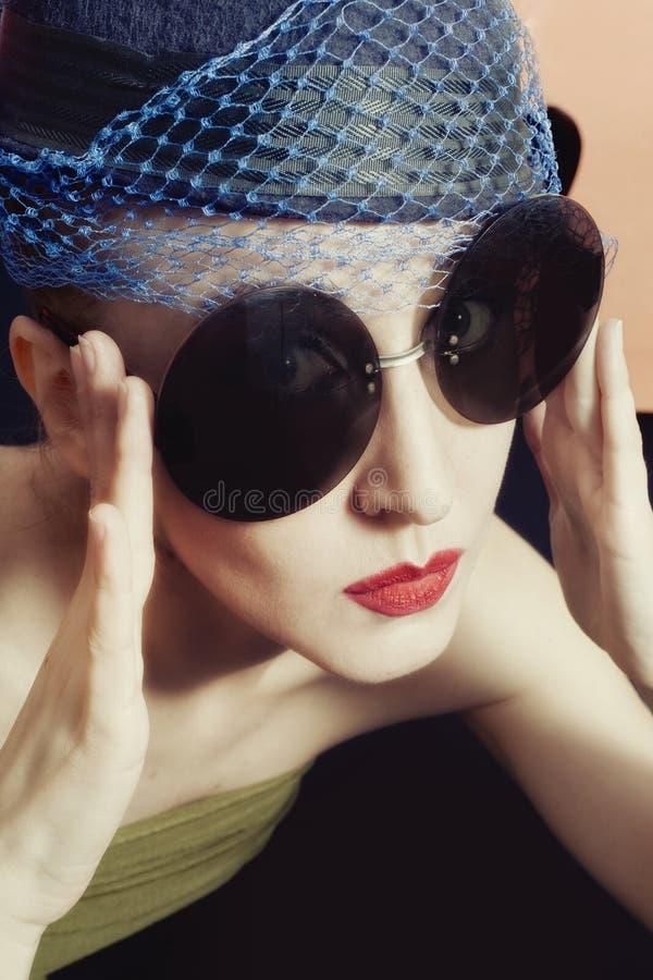 Νέες γυναίκες πορτρέτου στα πέπλα και τα στρογγυλά γυαλιά ηλίου στοκ φωτογραφίες