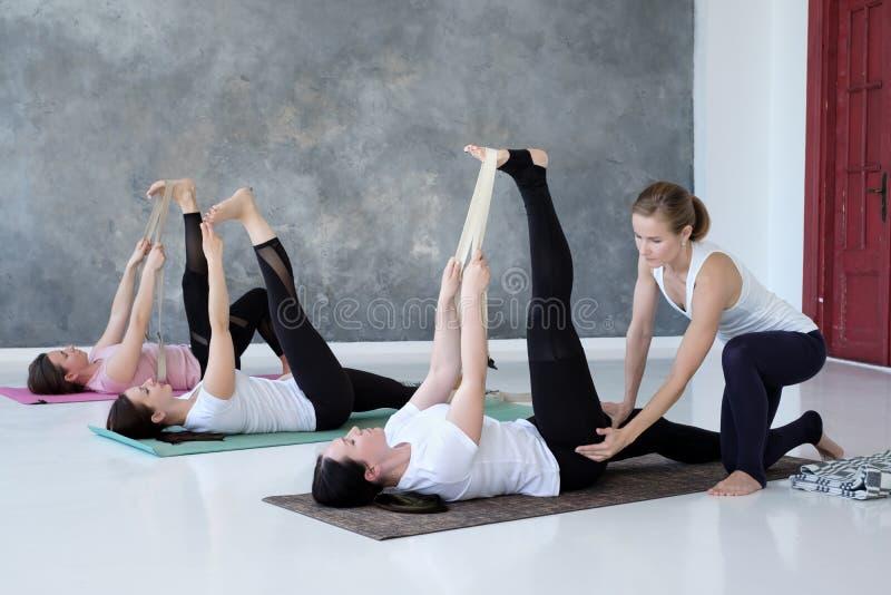 Νέες γυναίκες που επιλύουν κάνοντας την άσκηση στο πάτωμα σε Supta Padangushthasana στοκ εικόνα