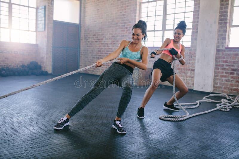Νέες γυναίκες που κάνουν το σχοινί που τραβά τις ασκήσεις σε μια γυμναστική στοκ φωτογραφίες