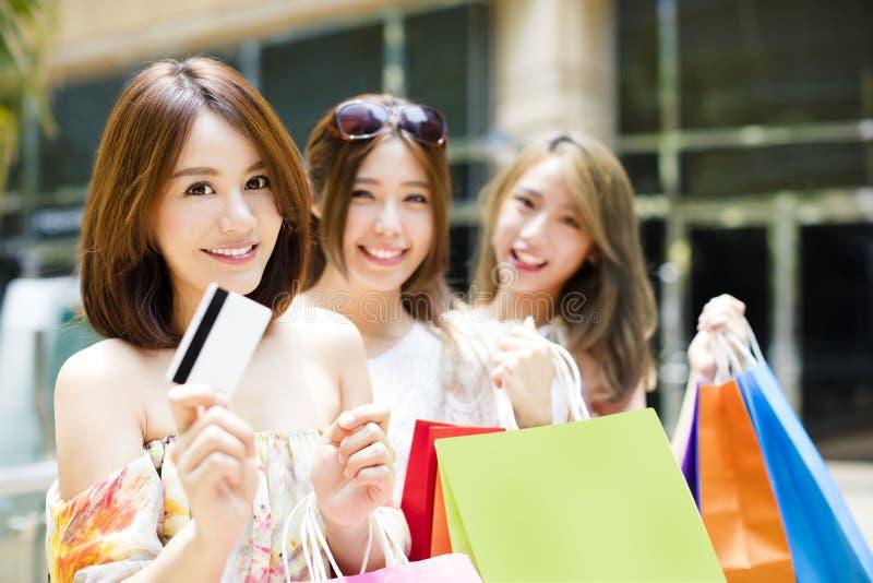 νέες γυναίκες που παρουσιάζουν τις τσάντες αγορών και πιστωτική κάρτα στοκ εικόνες