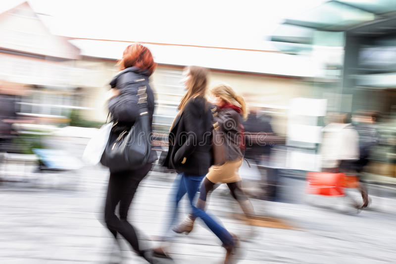 Νέες γυναίκες που περπατούν ενάντια στην προθήκη στο σούρουπο, επίδραση ζουμ, MO στοκ φωτογραφίες