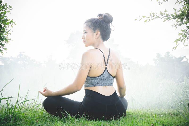 Νέες γυναικών άσκησης βοήθειες γιόγκας γιόγκας καθημερινές στη συγκέντρωση στοκ εικόνες με δικαίωμα ελεύθερης χρήσης