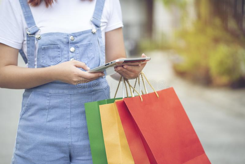 Νέες γυναικών χεριών εκμετάλλευσης τσάντες συσκευών και αγορών ταμπλετών έξυπνες με τη στάση στο χώρο στάθμευσης αυτοκινήτων στοκ φωτογραφίες με δικαίωμα ελεύθερης χρήσης