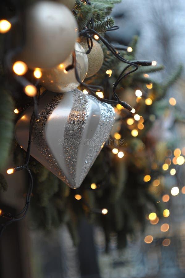 Νέες διακοσμήσεις έτους και Χριστουγέννων, παιχνίδια σε έναν κλάδο ενός χριστουγεννιάτικου δέντρου στοκ φωτογραφίες