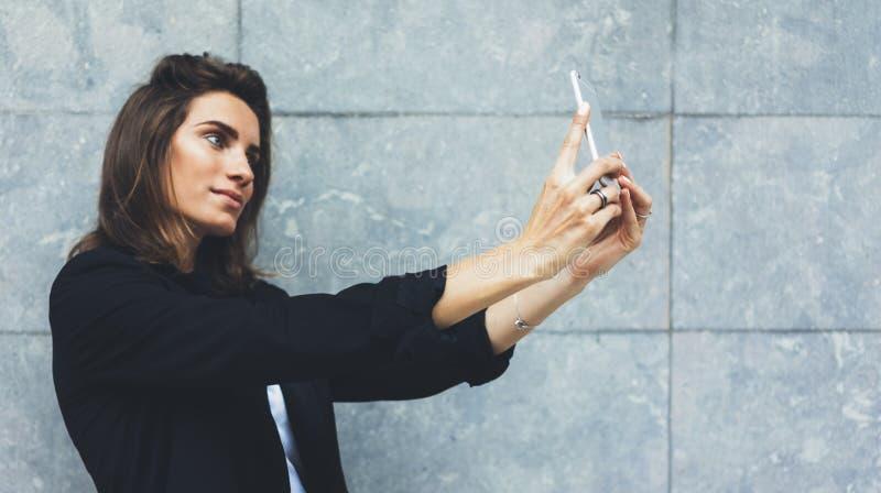 Νέες επιχειρηματίες πορτρέτου στο μαύρο κοστούμι που χρησιμοποιεί το smartphone στο συγκεκριμένο γκρίζο πρότυπο τοίχων υποβάθρου, στοκ φωτογραφία με δικαίωμα ελεύθερης χρήσης