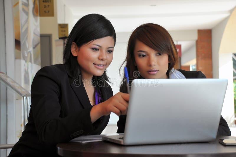 Νέες επιχειρηματίες που μοιράζονται τις πληροφορίες στο lap-top στοκ εικόνες