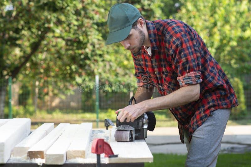Νέες εργασίες ξυλουργών με την ηλεκτρική μηχανή πλανίσματος στοκ φωτογραφία με δικαίωμα ελεύθερης χρήσης