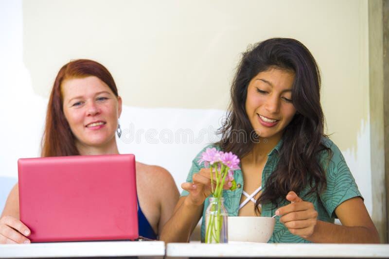 Νέες ευτυχείς και όμορφες καυκάσιες και λατινικές γυναίκες που εργάζονται στον καφέ γραφείων με το φορητό προσωπικό υπολογιστή πο στοκ φωτογραφίες