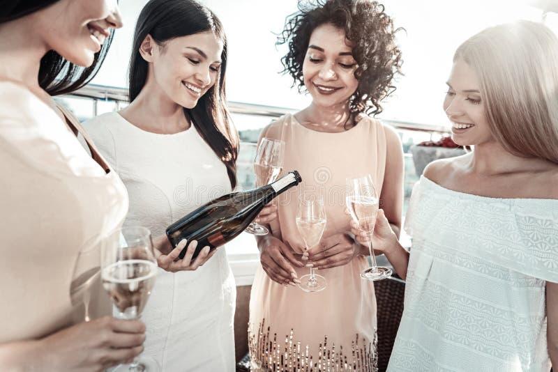 Νέες ευχάριστες κυρίες που κρατούν goblets της σαμπάνιας και της κατανάλωσης στοκ εικόνες