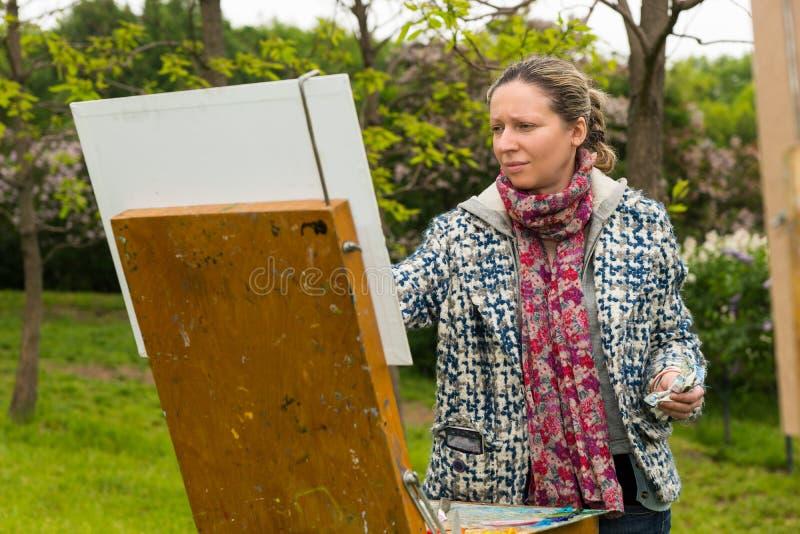 Νέες θηλυκές επίμονες τελευταίες πινελιές καλλιτεχνών paintig στο α στοκ εικόνες