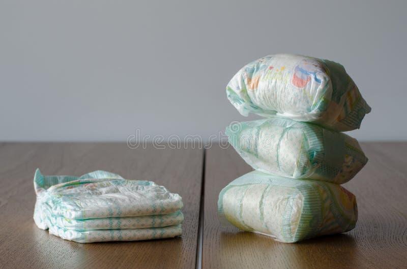 Νέες και χρησιμοποιημένες πάνες μωρών στο ξύλινο επιτραπέζιο υπόβαθρο στοκ εικόνα με δικαίωμα ελεύθερης χρήσης