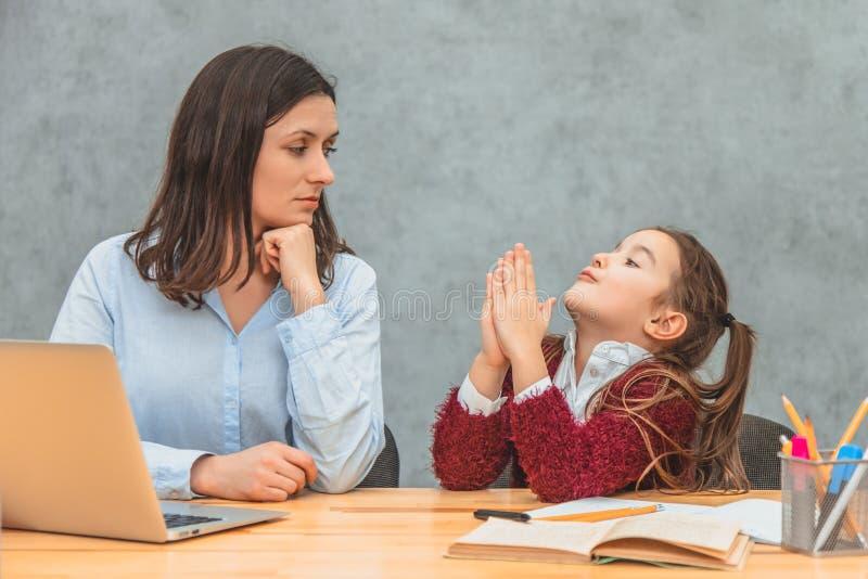 Νέες μητέρα και μαθήτρια σε ένα γκρίζο υπόβαθρο Τα χέρια κορών μου επάνω που ζητούν από τη μητέρα μου για να εξετάσει το lap-top  στοκ εικόνα