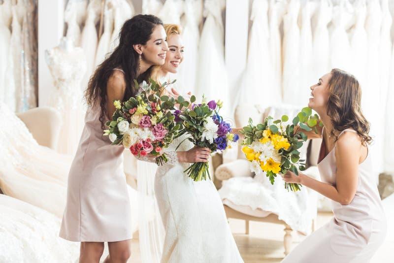 Νέες νύφη και παράνυμφοι που κρατούν τις τρυφερές ανθοδέσμες λουλουδιών στοκ εικόνες