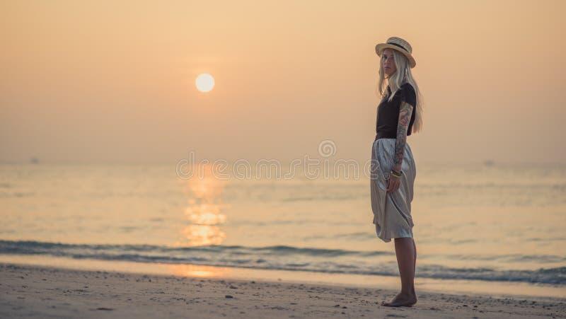 Νέες ξανθές στάσεις στην ακτή της θάλασσας και της εξέτασης πρωινού τη κάμερα ξυπόλυτο περπάτημα παραλιών στοκ φωτογραφία με δικαίωμα ελεύθερης χρήσης